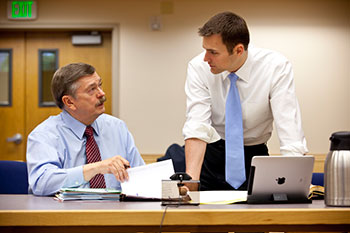Jim Nelsom and Dan Reyfield discuss a case inside of a courtroom.